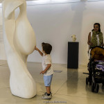 In the exhibition 'Risky travels' of Andys Hadjiadamos and Baci Bogac in Pafos on 5 May, 2017 for the Pafos 2017. The Andys grandson touching the sculpture of his grandfather and his mother looking.