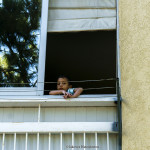 A picture taken in NICOSIA showing a young boy sitting in his window
