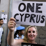 Turkish-Cypriot and Greek-Cypriot protestors hold banners during a demonstration outside the UN-controlled buffer zone in the Cypriot capital Nicosia on June 28, 2017, calling for the unification of the Mediterranean island after the Cypriot President warned of a possible impasse in talks to reunify the ethnically divided island.
